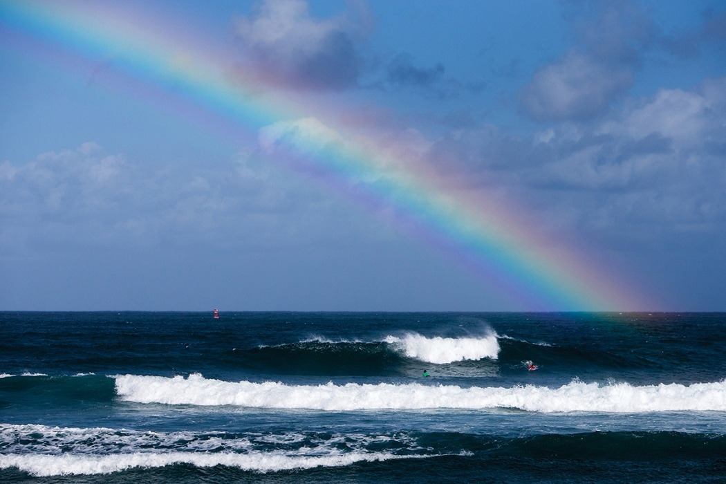 A rainbow appears over the lineup on day two of the Hawaiian Pro.   © WSL / Heff